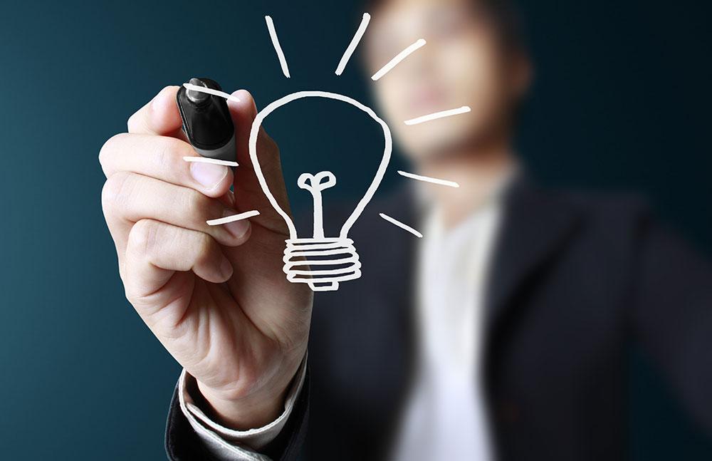 Homem desenhando um lâmpada - Ideias de negócios